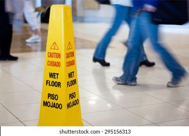 Caution Wet Floor sign with people walking in the background