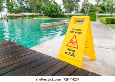 Caution wet floor sign at walkway around the swimming pool garden (yellow plastic stand with English and Thai text language)