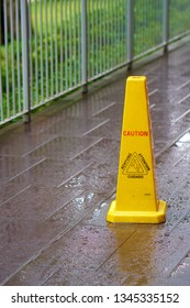 Caution! Wet floor. Slippery. Yellow plastic sign on the wet pavement.