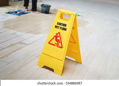caution wet floor warning sign with blurred worker mopping floor