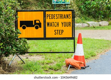 "A cautions sign that reads ""Pedestrians Watch Your Step"" and includes a symbol for a truck and a witches hat / traffic cone."