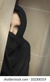 Cautious Islamic Woman in a Window Pane Wearing Traditional Burqa or Niqab.