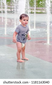 cautious toddler is a bit afraid to go into the fountains
