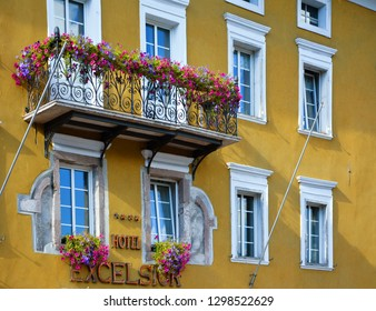 """Cavalese, Trentino, Italy, August 14, 2016: Partial view of the facade of the """"Excelsior"""" hotel, with windows, a balcony and flowers."""