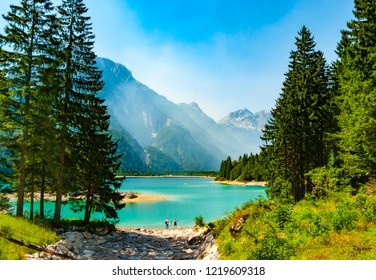 Cave del Predil lake framed by fir trees with haze embracing mountain sides, Friuli, Italy
