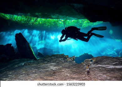 Cave Diver diving through the lights in a Cenote in Mexico