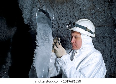 cave explorer examines the ice stalagmite on the background of a dark rocky wall covered with large icy crystals