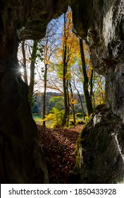 """Cave orifice of a limestone cave in the romantic """"Hönnetal"""" in Sauerland Germany in autumn season with colorful beech tree foliage an sunlight flashing into the darkness of the underground passage"""
