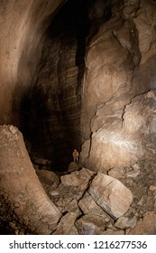 In the cave. Speleologist climbs the rope from great well.
