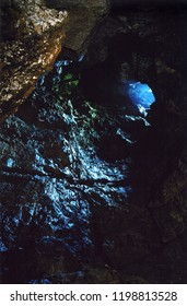 Cave. View from inside to the blue daylight of the entrance hole in the upper part of the cave.