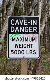 Cave-In Danger: Maximum Weight 5000 LBS sign which is placed over abandoned mines warning hikers of the dangers below.