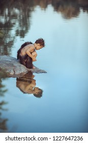 Caveman boy sitting on the rock and looking at him self in the water reflection in lake. Evolution survival concept. Creative art fantasy photo