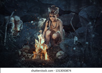 Caveman, manly boy at the fire. Scary young primitive boy outdoors near bonfire. Witch craft concept. Angry caveman, manly boy with horns near bonfire. Prehistoric tribal man outdoors on nature