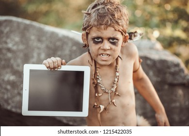 Caveman, manly boy holding tablet PC. Funny young primitive boy outdoors. Evolution degradation concept. Calm boy outside against rocky background. Prehistoric tribal man outside on wild nature with