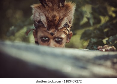 Caveman, manly boy hunting outdoors. Prehistoric tribal boy outdoors on nature. Young shaggy and dirty savage, warrior and hunter hiding in an ambush behind a stone. Primitive ice age man in animal