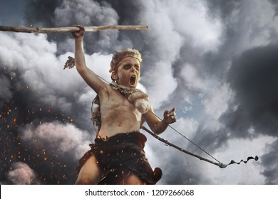 Caveman, manly boy with weapon aggressively shouting. Dramatic action photo of young primitive boy outdoors agaisnt dark clouds. Evolution survival concept. Calm boy outside standing in attack pose