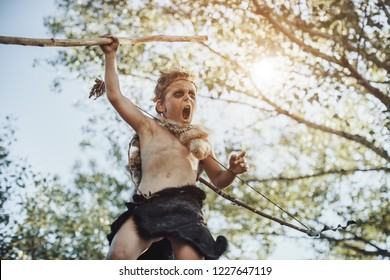 Caveman, manly boy with weapon aggressively shouting. Dramatic action photo of young primitive boy outdoors in forest. Evolution survival concept. Calm boy outside standing in attack pose. Prehistoric