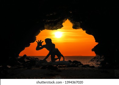 Caveman posture or action in the cave at red sky sunset background