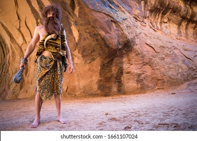 Caveman standing outdoors holding his club in an empty cave