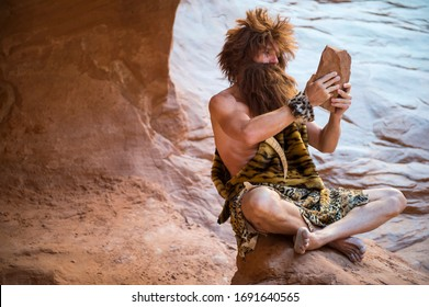 Caveman watching the screen of his primitive stone tablet outdoors in a weathered rock cave