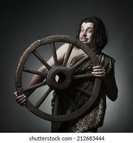 Caveman wearing leopard skin hold old wooden wheel.