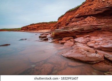 At Cavendish beach, on Canada's Prince Edward Island, the flat red sandstone has been weathered by winds and ocean currents. The red cliff overlooks the Atlantic ocean with a rolling hillside.