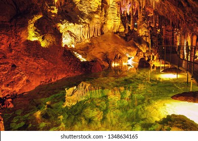 Caves in France. Grandes Canalettes in the French Pyrenees. Amazing view on stalactites in colorful bright light, beautiful natural attraction.