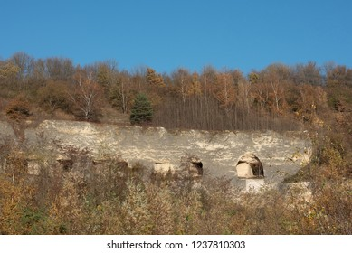 Caves in a wall in a yellow and grey marl quarry against a blue sky