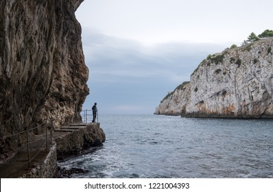 Caves of Zinzulusa, near Castro on the Salento Peninsula in Puglia, Southern Italy. Person in silhouette stands on the gang plank at the entrance.