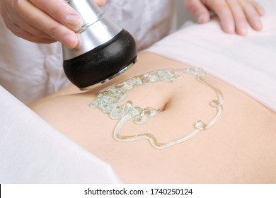 The cavitation procedure closeup. Beautician apparatus for cavitation on the woman's stomach. The concept of skin care face and body