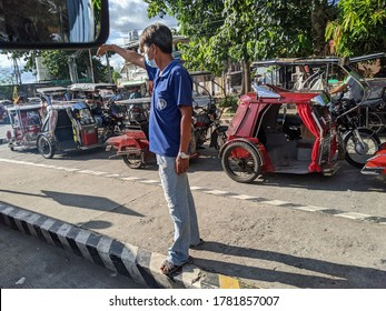 Cavite, Philippines - July 23, 2020: A Filipino calling for passengers to ride in his jeepney in the middle of the coronavirus pandemic.