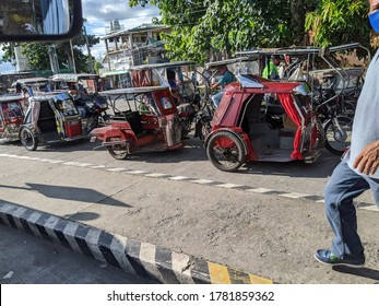 Cavite, Philippines - July 23, 2020: A man parking his tricycle, a common means of public or private transportation in the middle of the coronavirus pandemic.