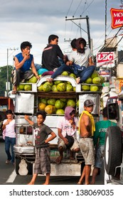 CAVITE, PHILIPPINES - MAY 14: Filipino workers escort a coconut packed Jeepney on May 14, 2009 in Cavite. The Philippines is the world's top producer of coconuts, in 2009 they produced 19,500,000 tons