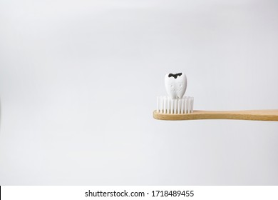 Cavity decayed tooth on wooden brown toothbrush on white background, How to prevent tooth decay and cavities
