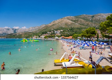 CAVTAT, CROATIA - JULY 17, 2015: Sunny landscape side view of many people sunbathing on a beach with buildings and mountains in the background in Cavtat Croatia July 17, 2015.
