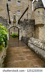 Cawdor, Nairn, Scotland, UK - June 16, 2018: Front of Cawdor Castle with turret and drawbridge with bell and Stags Head Buckel Be Mindfull emblem in the rain Cawdor Nairn Scotland UK