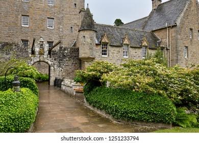 Cawdor, Nairn, Scotland, UK - June 16, 2018: Front of Cawdor Castle with drawbridge bell and Stags Head Buckel Be Mindfull emblem in the rain Cawdor Nairn Scotland UK