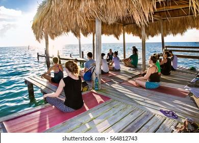 CAYE CAULKER, BELIZE - DEC 17 2015: Yoga at dock of Caye Caulker island on Dec 17, 2015, Belize. Participants perform yoga moves outdoors by the sea.