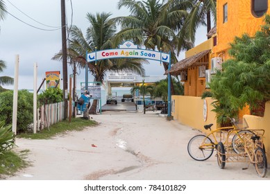 CAYE CAULKER, BELIZE - NOVEMBER 20, 2017: Caye Caulker Island in Caribbean Sea. Sandy Street with Local Architecture and Exit Sign Come Again Soon