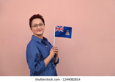 Cayman Islands flag. Business woman holding flag. Nice portrait of middle aged lady 40 45 years old with a national flag over pink wall on the city street outdoors.