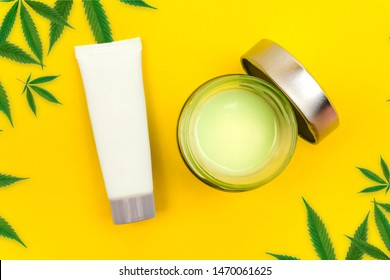 CBD cannabis balm and lotion with cannabis leafs on yellow background