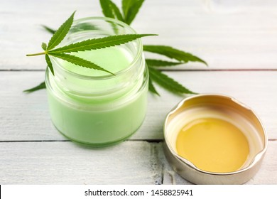 CBD Cannabis Hemp topical cream balm with cannabis leafs on wooden table