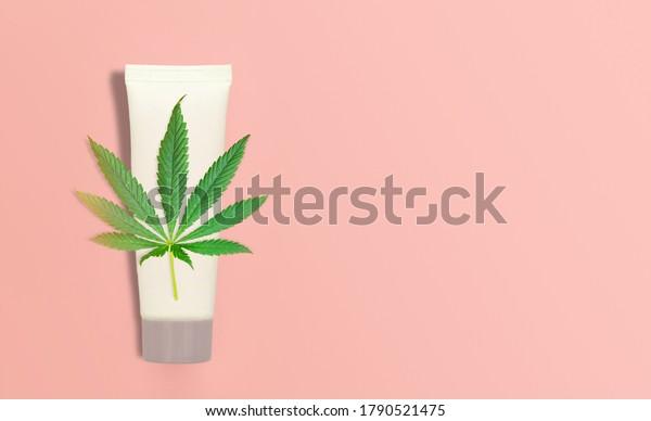 CBD Cannabis Hemp topical cream balm with cannabis leaf on pink backdrop