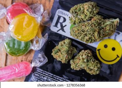 CBD infused hard candies next to trimmed marijuana buds.