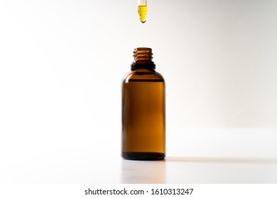 CBD oil or any other oil dropping into a small bottle - white background