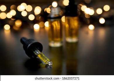 CBD-Öle fallen auf dunklem, launenhaftem Hintergrund mit dunkler Beleuchtung