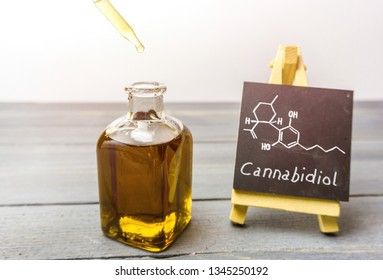 Cbd oil in glass bottle and chalkboard with molecule drawing on wooden table
