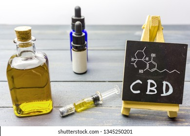 Cbd oil in glass bottle, hemp paste and chalkboard with molecule drawing on wooden table
