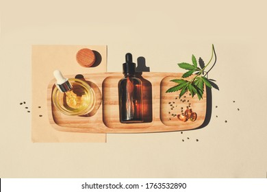 CBD oil, tincture with marijuana leaves on a beige background. Cannabis seeds in a wooden spoon. Medical cannabis concept for health and cosmetics. Minimalism.