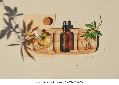 CBD oil, tincture with a pipette on a beige background with hemp leaves. Concept medical cannabis Trendy Flat Lay Minimalism